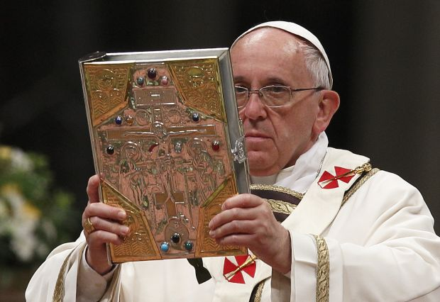 Pope Francis raises Book of Gospels as he celebrates Easter Vigil in St. Peter's Basilica at Vatican